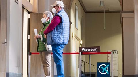 Ein Mann und eine Frau warten mit Maske vor einem Wahllokal.