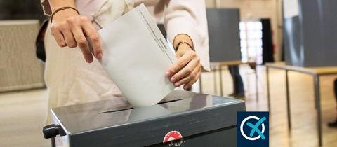 Eine Frau wirft ihren Stimmzettel in eine Wahlurne. Im Hintergrund ist unscharf das Wahllokal zu sehen.