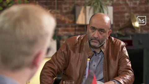 Omid Nouripour sitzt einer Person an einem Tisch gegenüber