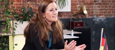 Janine Wissler sitzt in der hr-Wählbar an einem Tisch, spricht und gestikuliert mit ihren Händen.