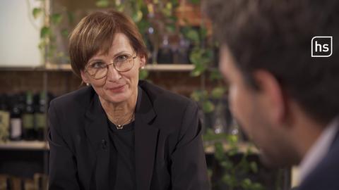 Politikerin Bettina Stark-Watzinger im Portrait, am Tisch sitzend im Gespräch