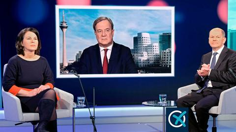 Annalena Baerbock und Olaf Scholz sitzen im Fernsehstudio in Sesseln, daneben kleine Tische mit Wassergläsern, bei einer Diskussionsrunde. Armin Laschet wird auf einem Fernsehschirm gezeigt.