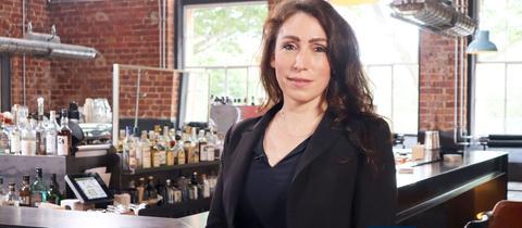 Mariana Harder-Kühnel steht vor einem Tresen in einer Bar und lächelt in die Kamera.