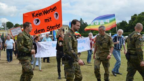 """Bundeswehr-Soldaten und Demonstranten mit """"Pace""""-Flagge."""