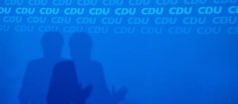 Kanzlerin Merkels Schatten auf einer CDU-Wand