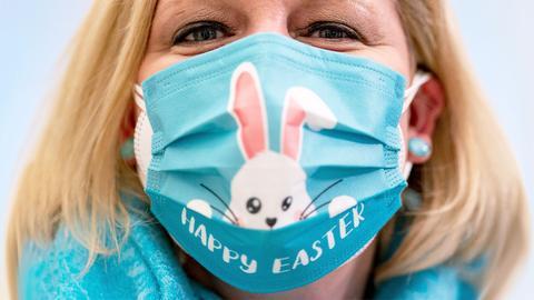 Eine Frau trägt einen Mund-Nasen-Schutz mit Ostermotiv.