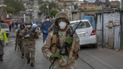 Soldaten patroullieren in einem dicht besiedelten Township in Südafrika