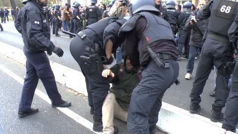Polizisten halten einen Mann bei der Demo auf dem Boden fest.