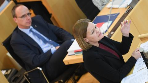 Nancy Faeser am Rednerpult, im Hintergrund Innenminister Peter Beuth.