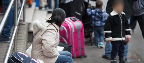Eine Mutter und ihre Sohn warten vor der Hessischen Erstaufnahmeeinrichtung für Flüchtlinge in Gießen
