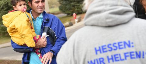 """Ein Flüchtlingshelfer im hessischen Büdingen mit """"Hessen: Wir helfen!""""-Pullover."""