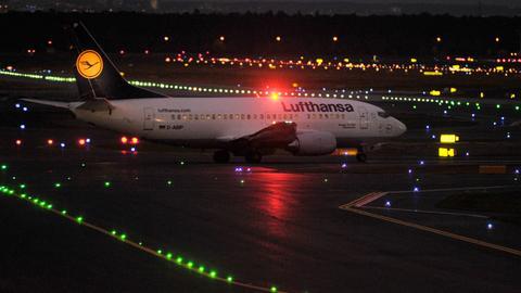 Eine Lufthansa-Maschine steht bei Nacht auf dem Rollfeld.