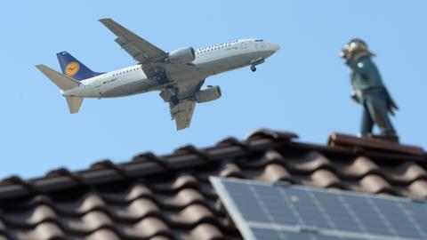 Flugzeug überfliegt ein Haus in Flörsheim, auf dem eine Schlafwandler-Figur steht.