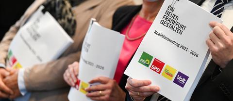 """Drei Menschen stehen nebeneinander und halten ein dickes Schriftstück mit dem Titel """"Ein neues Frankfurt gestalten"""" in der Hand. Am unteren Ende sind darauf die Logos der Parteien DIe Grünen, SPD, FDP und Volt zu sehen."""
