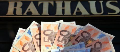 """Euro-Scheine vor einem """"Rathaus""""-Schriftzug."""