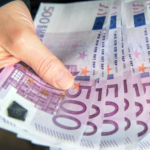 Zwei Hände fächern acht 500-Euro-Scheine auf