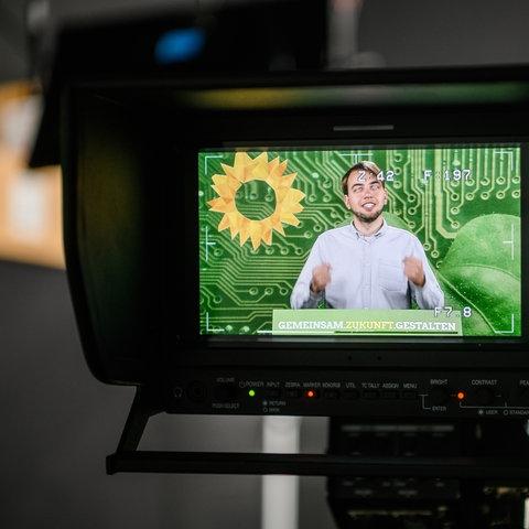 Foto einer Filmkamera, in deren Vorschau man den jungen Grünen-Politiker Philip Krämer während einer Rede sieht.