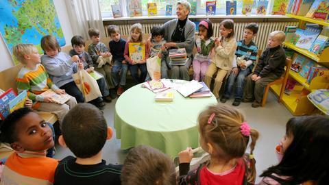 Lehrerin und Schüler im Lesezimmer einer Grundschule in Frankfurt