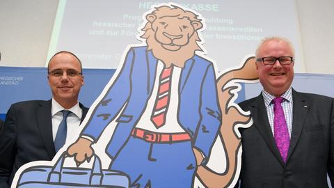 Innenminister Peter Beuth (li.) und Finanzminister Thomas Schäfer (re.) mit einem Hessen-Löwen, der eine Hessenkasse-Tasche trägt.