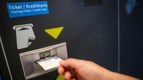Eine Hand zieht ein Ticket aus einem Parkgebührenautomaten
