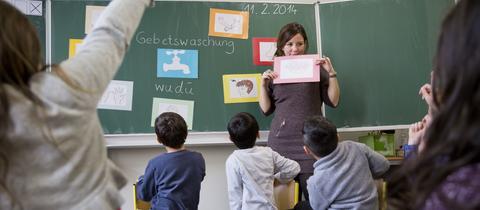 Eine Lehrerin erklärt Erstklässlern in einer Schule in Frankfurt im Islamunterricht die Gebetswaschung.