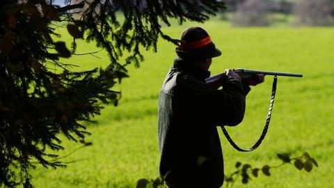 Ein Jäger mit Gewehr im Anschlag.