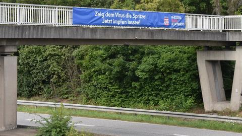 """Ein Banner mit der Aufschrift """"Zeig dem Virus die Spritze: Jetzt impfen lassen"""" hängt an einer Brücke, die über eine Straße führt."""