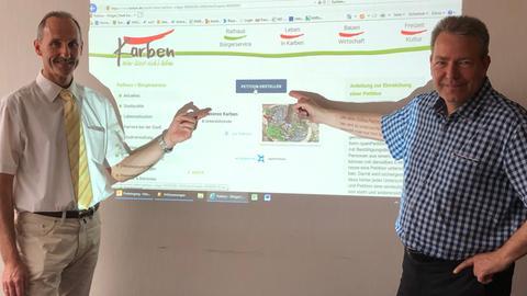 Karbens Bürgermeister Rahn und Verwaltungschef Schenk vor der Petitions-Seite der Stadt
