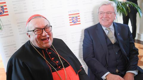 Kardinal Karl Lehmann lacht in die Kamera, im Hintergrund Ministerpräsident Volker Bouffier.