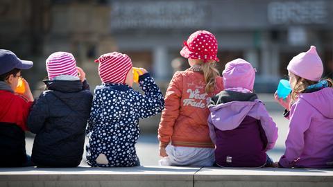 Kindergartenkinder sitzen in der Sonne.