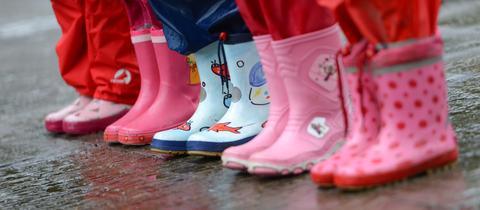 Kindergartenkinder stehen mit Gummistiefeln auf nassem Boden.