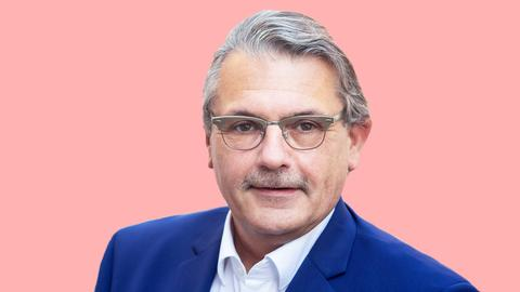 Ausgeschnittenes Portrait von Klaus Peter Schellhaas (SPD) auf einer rosafarbenen Fläche.