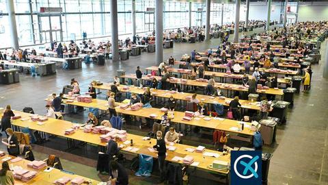 Unzählige Wahlhelfer*innen sitzen an sehr vielen Tischen in der riesigen Messehalle und zählen die Briefwahlstimmen aus (aus der Vogelperspektive fotografiert).
