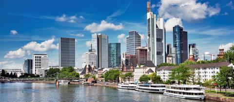 Foto der Frankfurter Skyline, im vordern Bild ist der Main zu sehen.