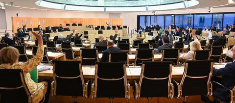 Abgeordnete sitzen im Plenarsaal des hessischen Landtags