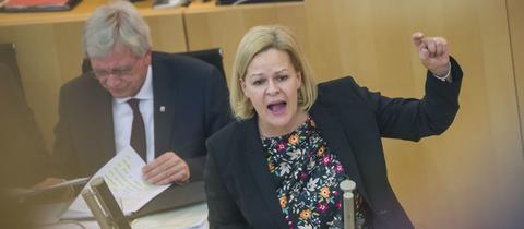 Ministerpräsident Volker Bouffier hört Oppositionsführerin Faeser im Landtag zu.