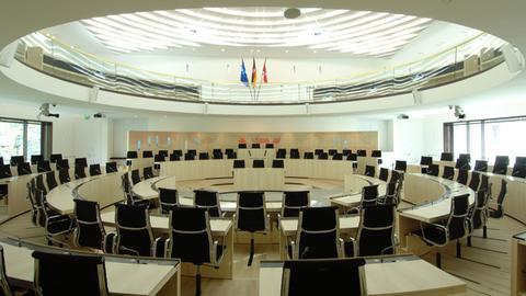 Das Foto zeigt den Plenarsaal des Hessischen Landtags mit leeren Sitzen.
