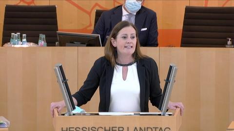 Janine Wissler steht am Rednerpult im hessischen Landtag und spricht.