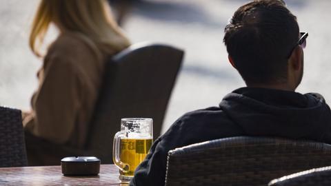 Ein Mann sitzt bei Sonnenschein in einem Restaurant.
