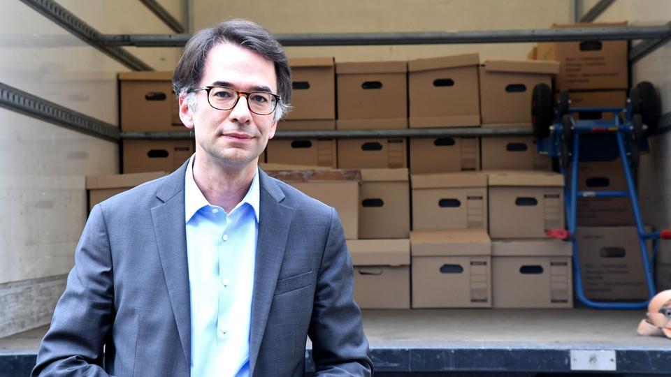 Der Ausschussvorsitzende Heinz (CDU) vor den Akten-Kartons im Lkw.