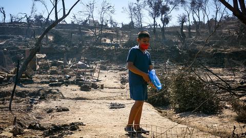 Ein Junge steht im abgebrannten Lager Moria auf Lesbos