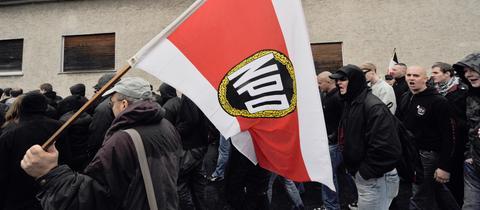 Demonstranten mit einer NPD-Fahne.