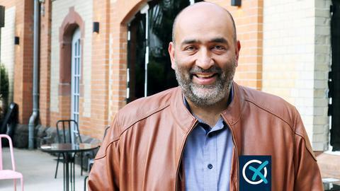 Omid Nouripour steht vor einer Bar in Gießen und lächelt in die Kamera.
