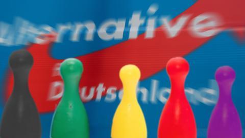 Parteien als Figuren, im Hintergrund ein AfD-Plakat