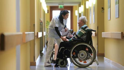 Eine Pflegeassistentin hilft einer Frau im Rollstuhl