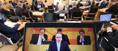 Im Vordergrund: Ein Tablet auf dem die Rede von Innenminister Beuth zu sehen ist. Dieser steht am Rednerpult des hessischen Landtags. Im Hintergrund ist das runde Plenum des Landtags zu erkennen. Die Abgeordneten sitzen mit dem Rücken zur Kamera.