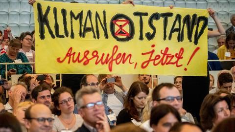 """Menschen halten ein gelbes Plakat mit der Aufschrift """"Klimanotstand ausrufen"""" hoch"""