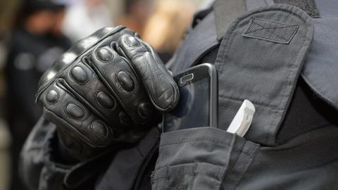 Polizist holt Handy aus der Tasche