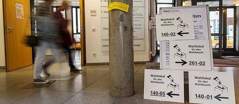 Menschen in einem Wahllokal in Frankfurt zum Bürgerentscheid über die Rennbahn.