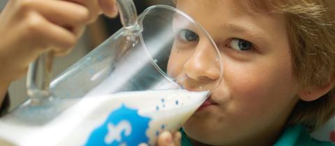Ein Junge trinkt aus einem großen Glas Schulmilch